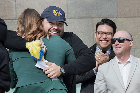 UC Irvine medical student is overjoyed to learn he has goes to his first choice of residency programs, UC Irvine Emergency Medicine. He hugs a relative as as Drs. Warren Wiechmann and Chris Fox cheer him on.