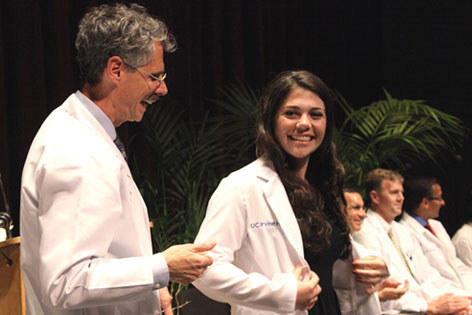 UC Irvine Vice Chancellor Howard Federoff congratulates a new medical student who has just received her white coat at the annual ceremony for incoming students.